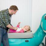 Dokter van Loenen laat een kind tijdens onderzoek lachen